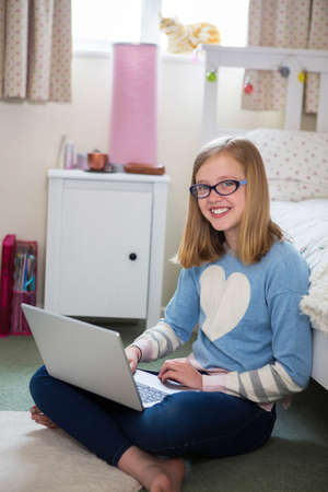Portrait Of Girl Sitting On Floor Of Bedroom Using Laptop Stock Photo