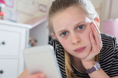 Young Girl Victim Of Bullying By Text Message Lying On Bed At Home
