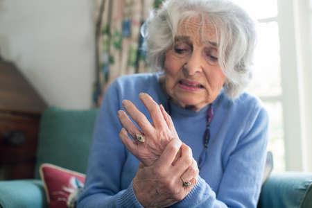 Senior vrouw thuis met lijden aan artritis