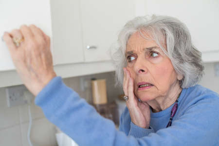 Forgetful Senior Woman With Dementia Looking In Cupboard Stock Photo