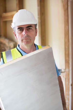Portrait Of Builder Fitting Insulation Boards Into Roof Of New Home Stock Photo
