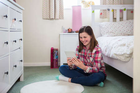 Girl Sitting On Floor Of Bedroom Using Digital Tablet