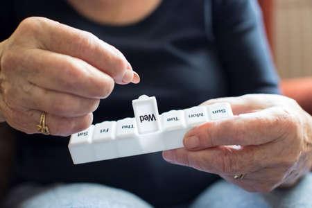 알약 상자에서 약을 복용하는 수석 여자 스톡 콘텐츠