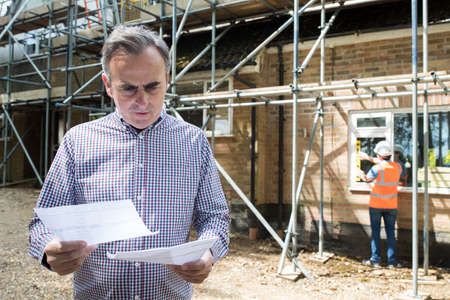 Worried Client Looking At Bills For House Building Work