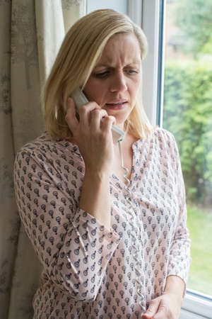 Worried Woman Answering Telephone At Home Stock Photo