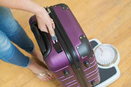 休日の前に規模でスーツケースの重量を量る女性のクローズ アップ
