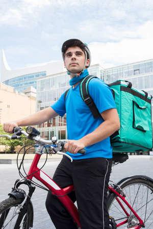 Courier en la bicicleta que entrega la comida en ciudad