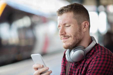 mp3 player: Man At Railway Station Using Mobile Phone On Platform