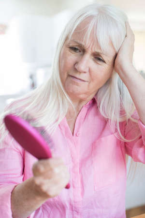 Senior Woman With Brush Concerned About Hair Loss