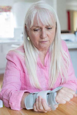 집에서 손목 부상으로 고통받는 성숙한 여인