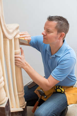 Carpenter Using Sandpaper On Bannister In Home