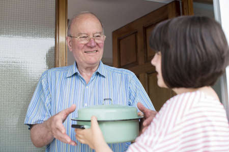 Teenage Girl Bringing Meal For Elderly Male Neighbour Stock Photo