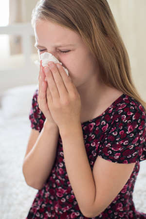 Girl Suffering With Cold Sneezing Into Tissue