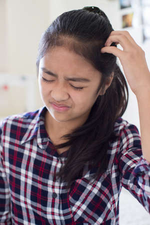 Young Girl Itching Scalp In Bedroom