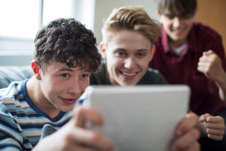 Three Teenage Boys Playing Game On Digital Tablet At Home 版權商用圖片 - 84915504