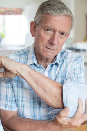 Portrait Of Mature Man Putting Ice Pack On Painful Elbow Stock Photo