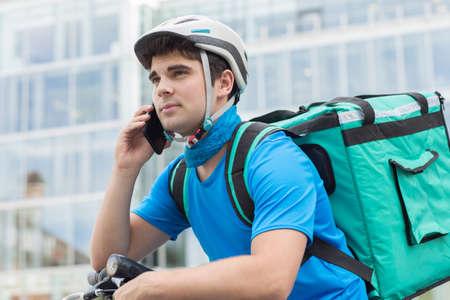 휴대 전화를 사용하여 도시에서 음식을 배달하는 자전거의 택배