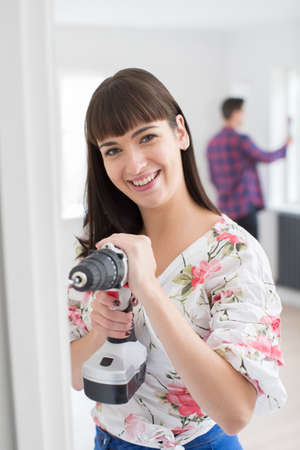 Woman Using Electric Drill As Couple Renovate Property Together
