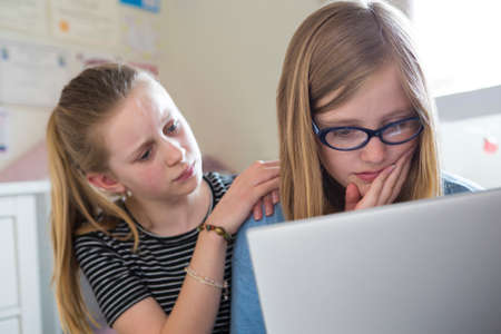 Pre Teen Girl With Friend Being Bullied On Line Stock Photo