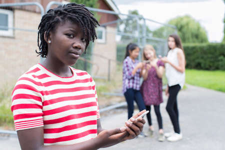 Portrait Of Teenage Girl Being Bullied By Text Message