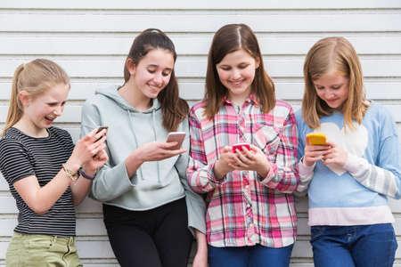 Gruppe junge Mädchen, die draußen Nachrichten auf Handys betrachten