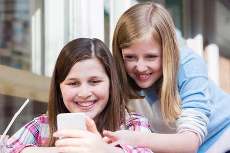 Zwei junge Mädchen am Café-Lesetextnachricht am Handy