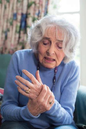 Ältere Frau zu Hause, die mit Arthritis leidet