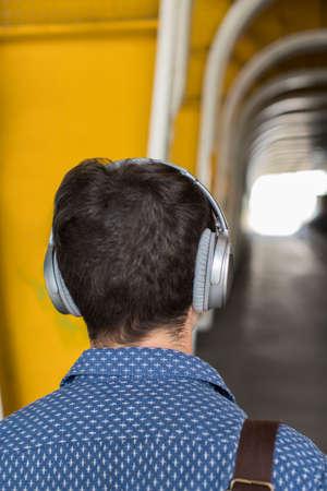 Rear View Of Man In Urban Setting Wearing Headphones