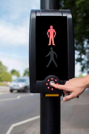 Hand Drücken der Taste auf Fußgängerüberweg