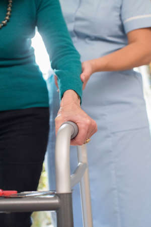 Senior Womans Hands On Walking Frame With Care Worker In Background