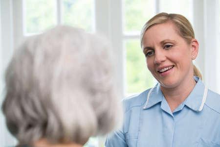 Pflegekraft, die zu Hause mit älterer Frau spricht