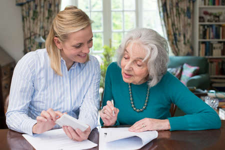 Woman Helping Senior Neighbor doing Paperwork