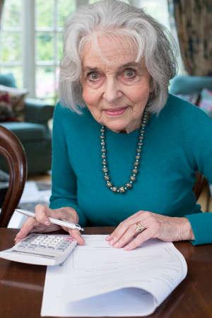 Lächelnde ältere Frau, die zu Hause Rechnungen durchläuft
