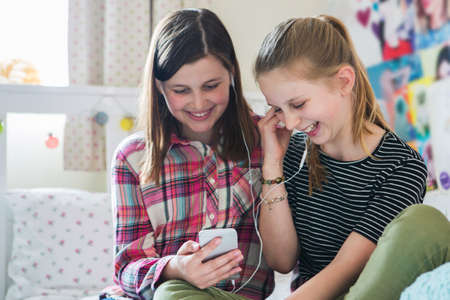 Two Girls Streaming Music From Mobile Phone In Bedroom
