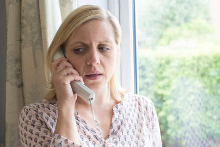 Worried Woman Answering Telephone At Home Standard-Bild