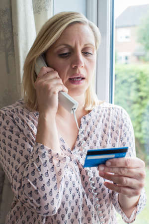 Mature Woman Giving Credit Card Details On The Phone Foto de archivo