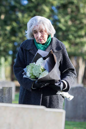 Sad Senior Woman With Flowers Standing By Grave