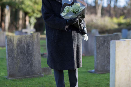 Close Up Of Senior Woman With Flowers Standing By Grave