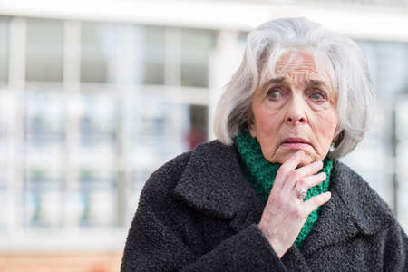 Worried Senior Woman Looking Lost Outdoors Banque d'images