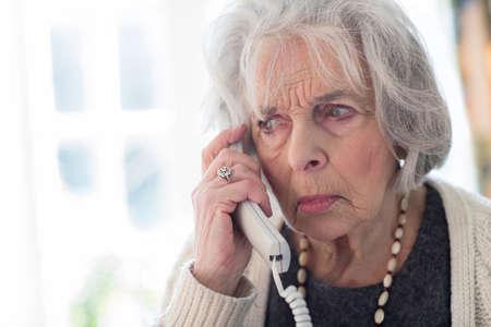 집에 전화 응답 걱정 고위 여자 스톡 콘텐츠