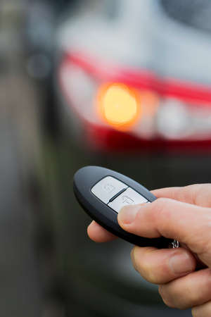 Close Up Of Driver Activating Car Security System With Key Fob Stock Photo