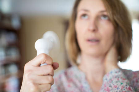 Mature Woman Experiencing Hot Flush From Menopause Using Electric Fan