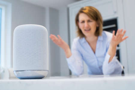 Frustrated Woman In Kitchen Asking Digital Assistant Question