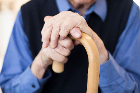 Close Up Of Senior Man's Hands Holding Walking Cane