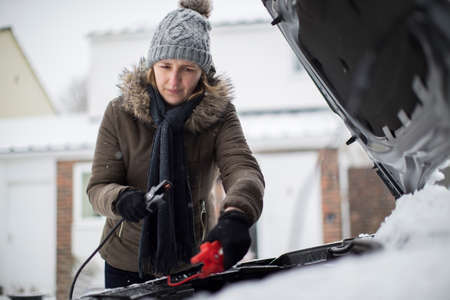 Woman Using Jumper Cables On Car Battery On Snowy Day