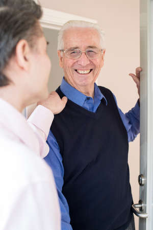 Man Checking On Elderly Male Neighbor Banque d'images