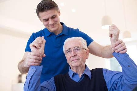 Male Nurse Assessing Senior Stroke Victim By Raising Arms