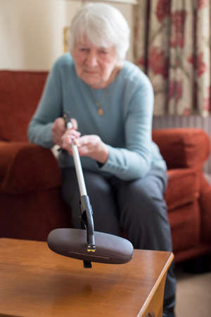 Senior Woman Using Reaching Arm To Pick Up Spectacles Case At Home