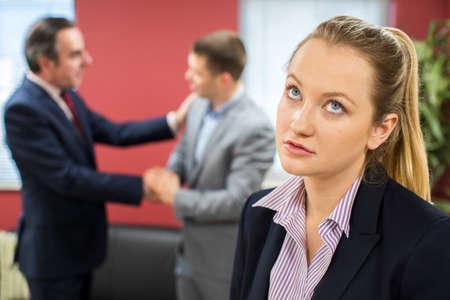 Unhappy Businesswoman With Male Colleague Being Congratulated Archivio Fotografico