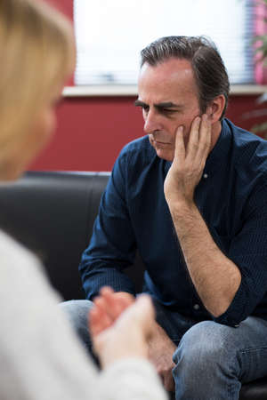 Depressed Mature Man Talking To Counselor Stock Photo